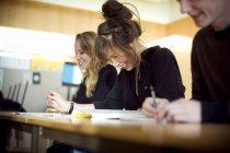 Усміхаючись студентів, що навчаються на столі в класі — стокове фото