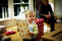 Little boy holding Christmas present with senior man in background at home — Stock Photo