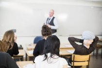 Professor teaching in classroom with students at high school — Stock Photo