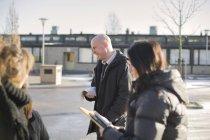 Lächelnden Lehrer Gespräch mit Schülerinnen und Schüler auf Straße — Stockfoto