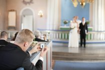 Man photographing bride and groom — Stock Photo