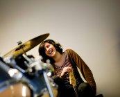 Смеющаяся женщина держит бас-гитару возле барабана в студии — стоковое фото