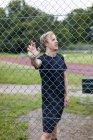 Спортсмен, стоящий у забора — стоковое фото