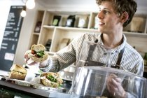 Young waiter serving sandwich — Stock Photo