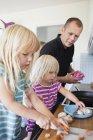 Дочь режет сосиски на кухне — стоковое фото