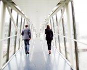 Business people walking on elevated walkway — Stock Photo
