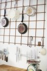 Cooking utensils hanging on wall — Stock Photo