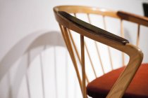 Wooden chair by white wall — Stock Photo