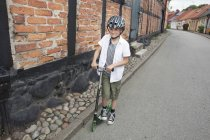 Счастливый мальчик катается на самокате — стоковое фото