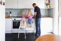 Vater und Töchter arbeiten in Küche — Stockfoto