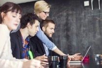 Creative business people using laptop — Stock Photo