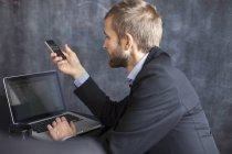 Uomo d'affari che utilizza il telefono cellulare — Foto stock