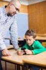 Teacher looking at schoolboy — Stock Photo