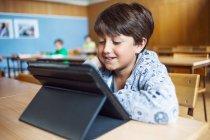 Усміхаючись школяр, використовуючи цифровий планшетний — стокове фото