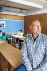 Thoughtful teacher sitting on desk — Stock Photo