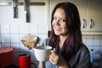 Happy woman holding coffee cup — Stock Photo