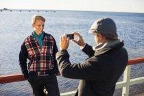 Man photographing happy gay partner — Stock Photo