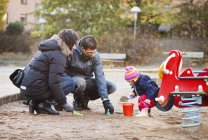 Family playing in sand — Stock Photo