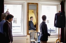 Fashion designer looking at male customer — Stock Photo