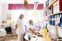 Medico e infermiere guardando monitor del computer — Foto stock