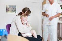 Ребенок с матерью и врачом — стоковое фото