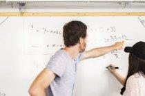 Student writing on whiteboard — Stock Photo