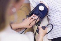 Doctor measuring blood pressure — Stock Photo
