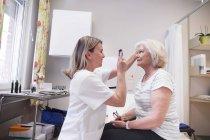 Doctor examining eyes — Stock Photo