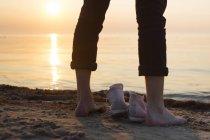 Homme debout au bord de mer au coucher du soleil — Photo de stock