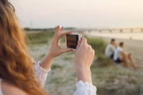 Young woman taking photo on beach — Stock Photo