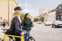Young women pushing bikes in town — Stock Photo