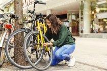 Jovem mulher bloqueando bicicleta — Fotografia de Stock