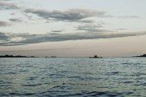 Пейзаж с силуэт гребная лодка — стоковое фото