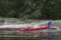 Donna che tira kayak sulla riva del lago — Foto stock