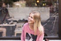 Mujer sonriente frente a la cafetería - foto de stock