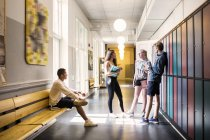 Young Students standing in corridor — Stock Photo