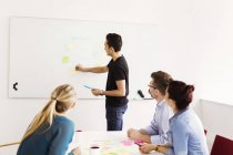 Colleagues looking at coworker writing on whiteboard — Stock Photo