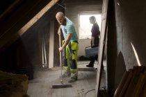 Homem varrendo sótão velho — Fotografia de Stock