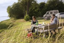 Family sitting at picnic table — Stock Photo
