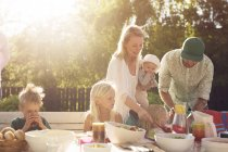 Family with four children at picnic table — Stock Photo