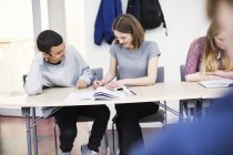Students sitting in classroom and writing in notebooks — Stock Photo