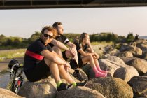 Cyclists sitting on coastline at sunset — Stock Photo