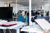 Smiling woman sitting in office interior — Stock Photo