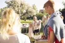 Family having garden party in back yard — Stock Photo