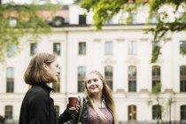 Zwei Studenten sprechen im Hof der Universität mit Tasse Kaffee — Stockfoto