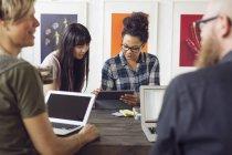 Mitarbeiter mit Notebooks am Tisch sitzen — Stockfoto