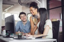 Coworkers smiling in front of computer — Stock Photo