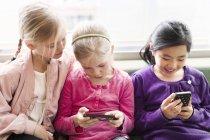 Tre ragazze sedute con gli smartphone — Foto stock