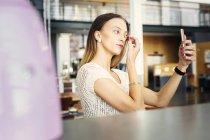 Женщина исправляет макияж — стоковое фото