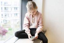 Garota sentada no peitoril da janela com smartphone — Fotografia de Stock